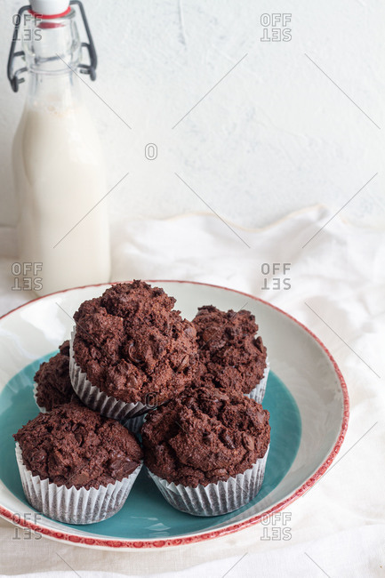 High angle tasty sweet chocolate cupcakes heaped on plate near jar with fresh milk in light kitchen