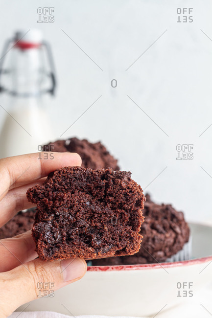 Crop anonymous person demonstrating half of yummy homemade chocolate muffin in light kitchen