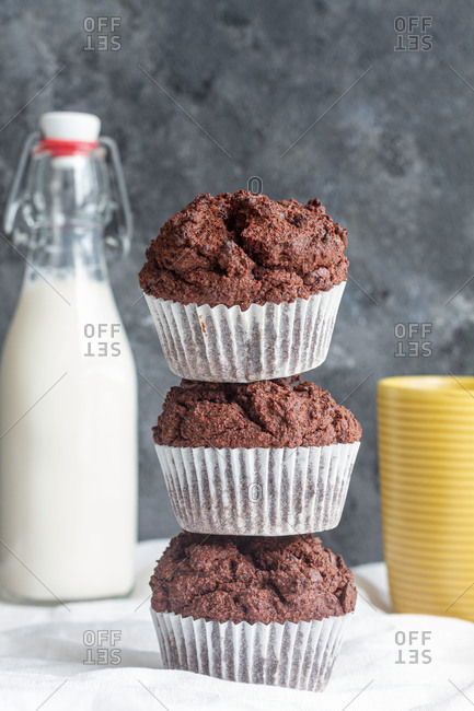 Delicious homemade chocolate muffins heaped on table in light kitchen