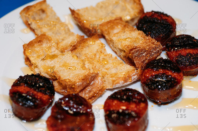 Closeup of sliced and grilled traditional Spanish chorizo sausage served with pieces of crusty bread