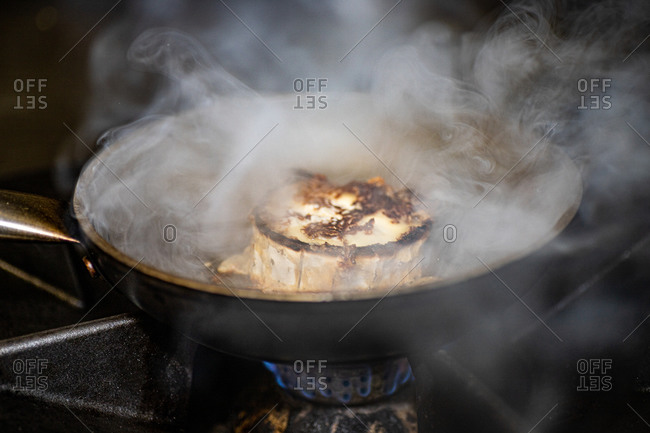 Steaming seared cheese being prepared in iron frying pan on gas stove in restaurant kitchen