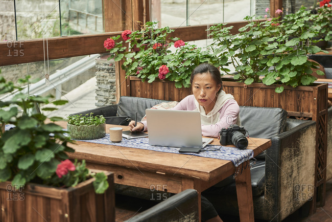 Concentrated Asian female journalist sitting at table with digital photo camera and using laptop while preparing new article