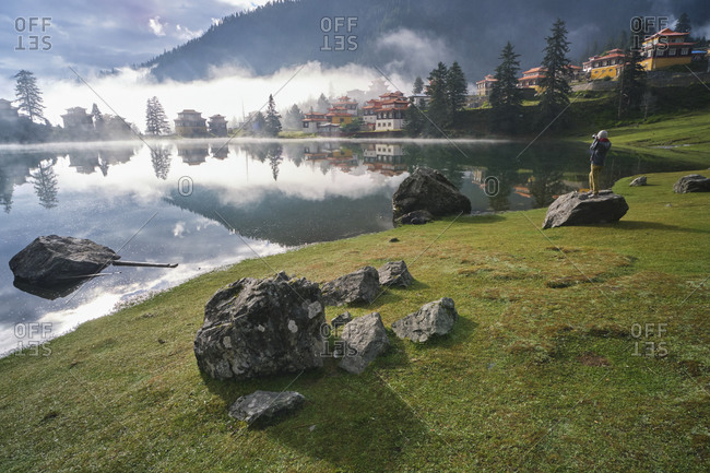 Scenery view of old buildings of Tibetan Buddhist temples located on shore of tranquil reflecting lake in highland covered with clouds