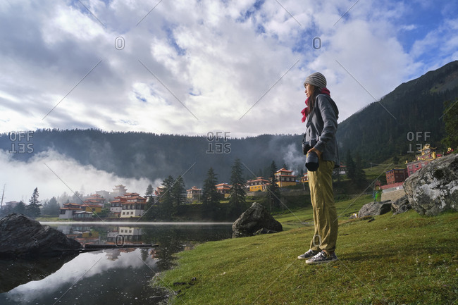 Low angle full body of calm Asian woman with professional photo camera standing on grassy coast of lake against Tibetan Buddhist temple