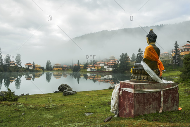 Statue of Buddha placed near peaceful Cuoka Lake located in green valley with high mountains and Tibetan Buddhist temple