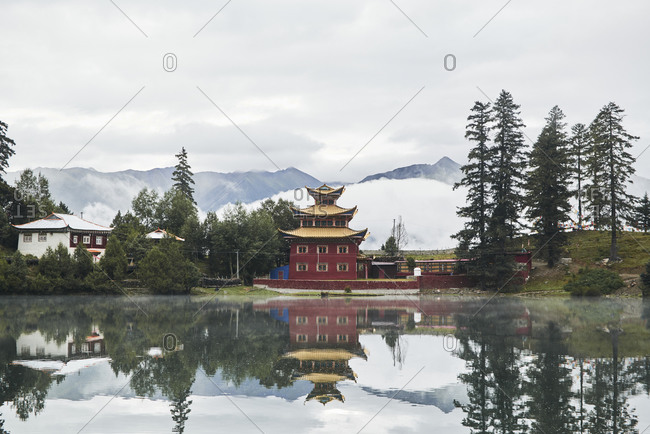 Picturesque scenery of Buddhist temple located on shore of calm Cuoka Lake with reflecting water surface in Chinese highland province