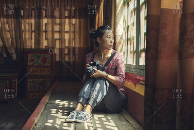 full body of Asian female photographer looking through window while resting in meeting place in Buddhist shrine