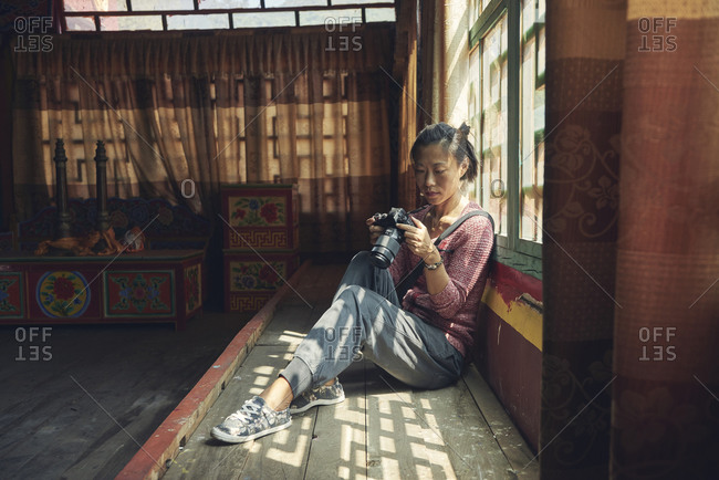 Side view full body of Asian female photographer looking through photos on camera while resting in meeting place in Buddhist shrine