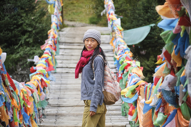 Young ethnic female tourist in warm clothing and hat looking at camera while crossing simple long narrow suspension wooden bridge decorated with bright multi colored pieces of fabric in daylight