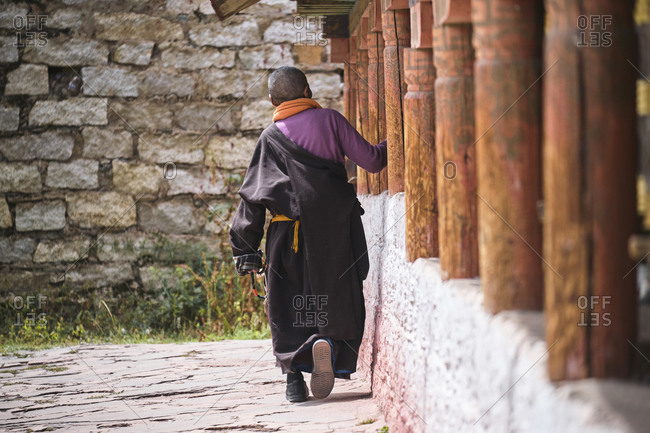 Back view of bald person in traditional colorful wearing near ancient oriental inscriptions