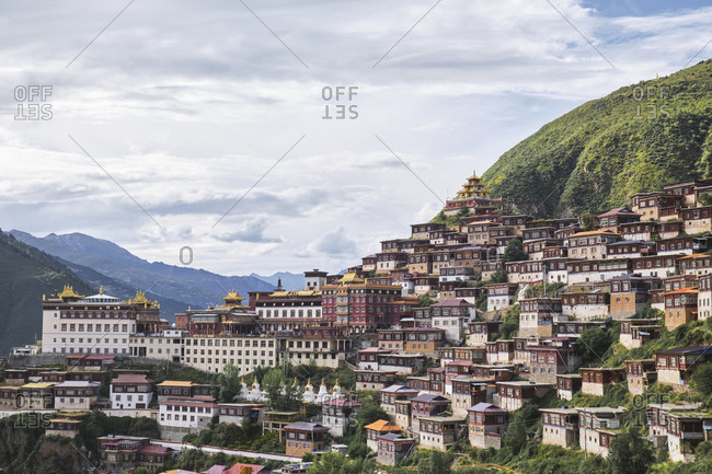 From above of row small wooden red houses randomly constructed on foot of tall slope covered with mountain forest