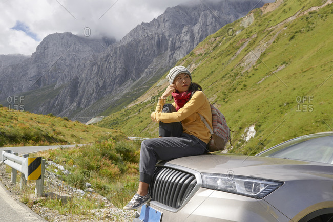 Asian female in scarf and yellow sweatshirt sitting on car hood and observing picturesque landscape of foggy mountains and looking away