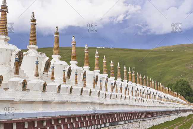 Ancient brick wall of oriental shrine located in green endless valley under blue tranquil sky in Sichuan province