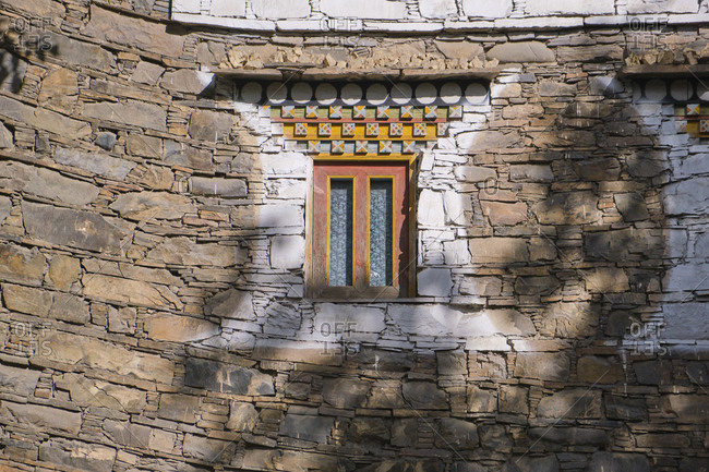 Exterior of aged stone house with weathered small window in Sichuan province of China. Tibetan village near to Maerkang, called Barkam in Tibetan, in between high mountains