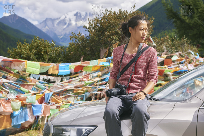 Young Asian female looking away and participating in rural celebrations with bright flags in high snowy rocky mountains of China