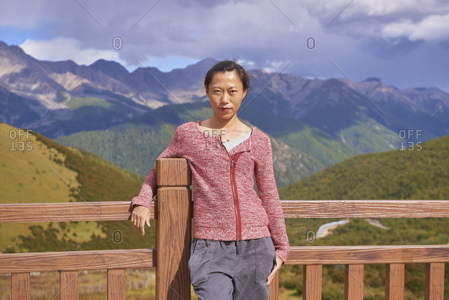 Young cheerful Asian female resting on balcony in picturesque scenery of high misty rocky mountains in green valley