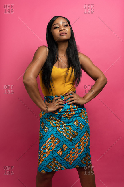 Self assured young black female in stylish outfit standing in pink studio with hands on waist and looking at camera
