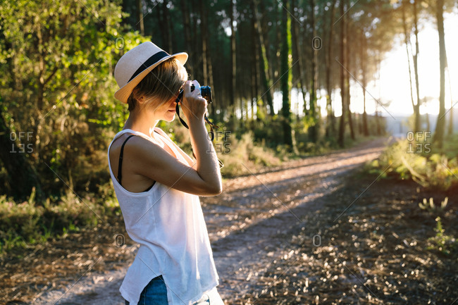 Side view of unrecognizable female photographer in casual outfit and hat standing on path in green forest and taking pictures on sunny day