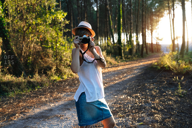Unrecognizable female photographer in casual outfit and hat standing on path in green forest and taking pictures on sunny day