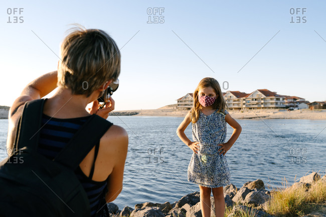 Back view of anonymous female traveler in casual clothes and face mask taking photo of little daughter standing on rocky coast of sea at sunset