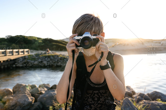 Peaceful adult female tourist with short hair in casual clothes and backpack standing on rocky coast of sea with photo camera wearing medical mask