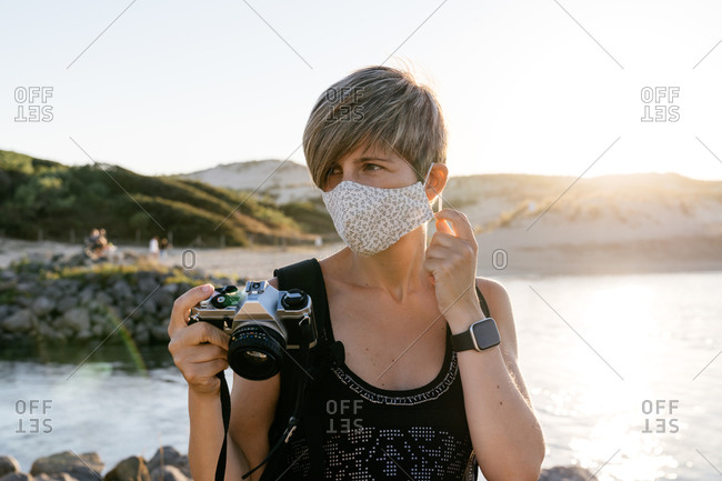Peaceful adult female tourist with short hair in casual clothes and backpack standing on rocky coast of sea with photo camera in hand and taking off medical mask