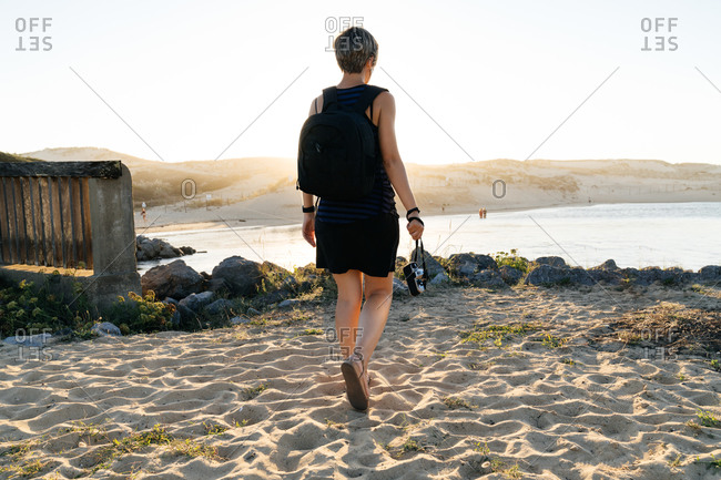 Back view of unrecognizable female traveler with photo camera and backpack in casual clothes and face mask recreating on rocky seashore during coronavirus