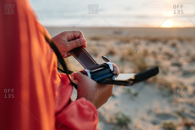 From above of crop anonymous female traveler setting vintage film camera while standing on sandy beach at sunset