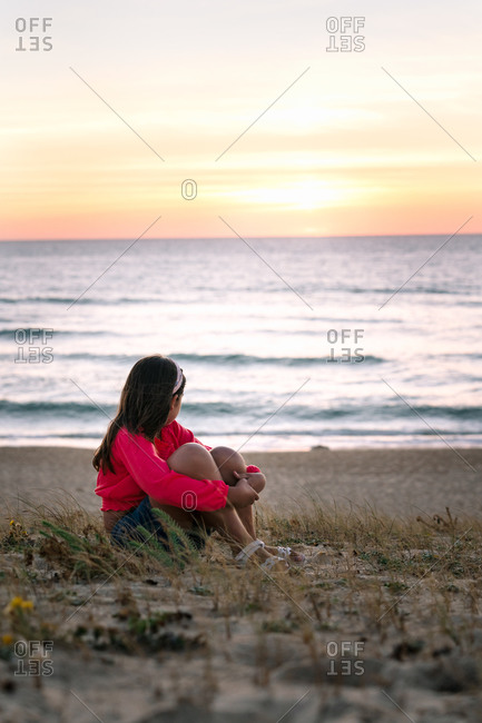 Side view of anonymous girl in stylish outfit embracing knees while resting on sandy beach and enjoying seascape at sunset