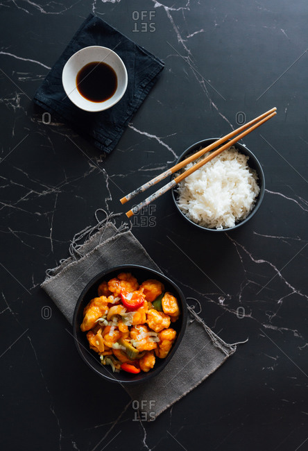 Top view of bowls with delicious rice and sweet and sour chicken dish placed on table with Asian chopsticks and soy sauce