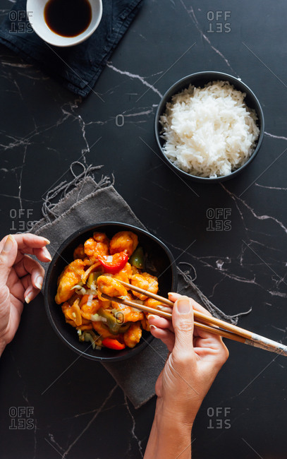 From above of crop unrecognizable woman eating appetizing Asian chicken dish and rice with chopsticks in stylish restaurant