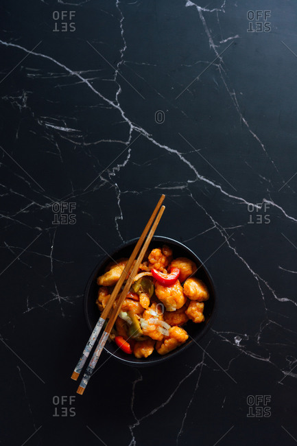 From above of tasty sweet and sour chicken with red and green bell pepper and onion in bowl with chopsticks placed on marble table