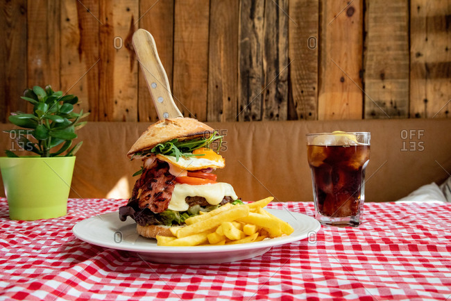 Appetizing burger with vegetables and cutlet on plate with French fries served on table with glass of cold coke in rustic cafe
