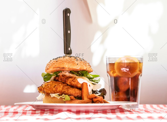 Appetizing chicken burger with vegetables and cutlet on plate with French fries served on table with glass of cold coke in rustic cafe
