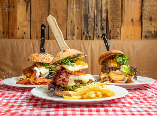 Various appetizing burgers with vegetables and cutlet on plate with potatoes served on table in rustic cafe