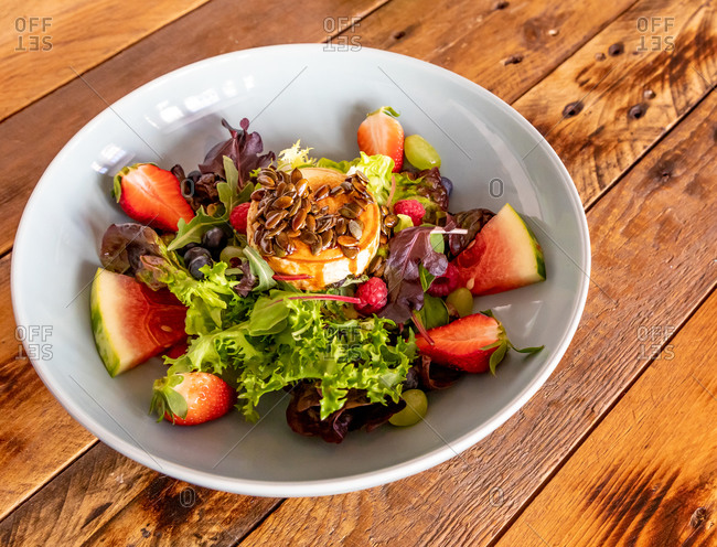 High angle of goat roller cheese salad served on plate with various fruits and fresh greenery on wooden table in cafe