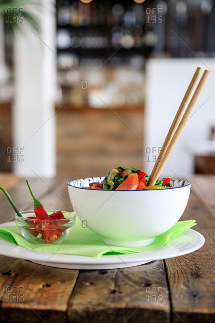 Bowl with appetizing salad and chopsticks placed on plate with red chili pepper served on wooden table in Asian cafe