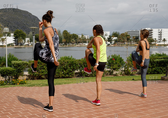 Back view of sportswomen moving actively while doing cardio workout together on embankment on sunny day