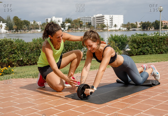 Slim female athlete doing exercises with ab wheel with support of personal trainer during workout in city