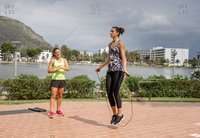 Determined female athlete skipping rope during active workout under supervision of professional personal trainer