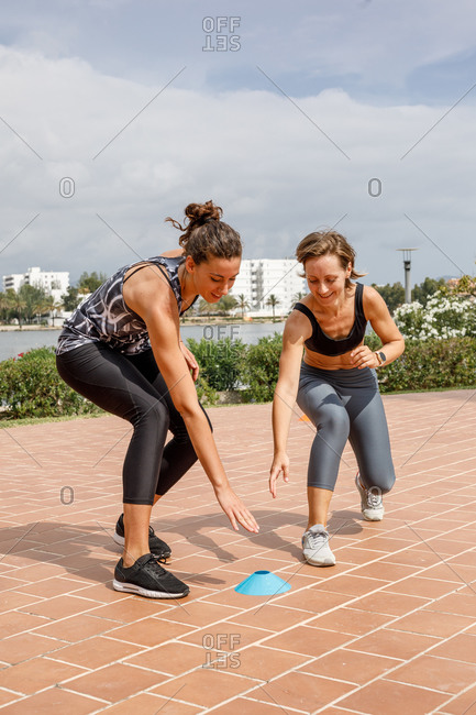 Cheerful female athletes running during dynamic workout while competing with each other under personal trainer supervision