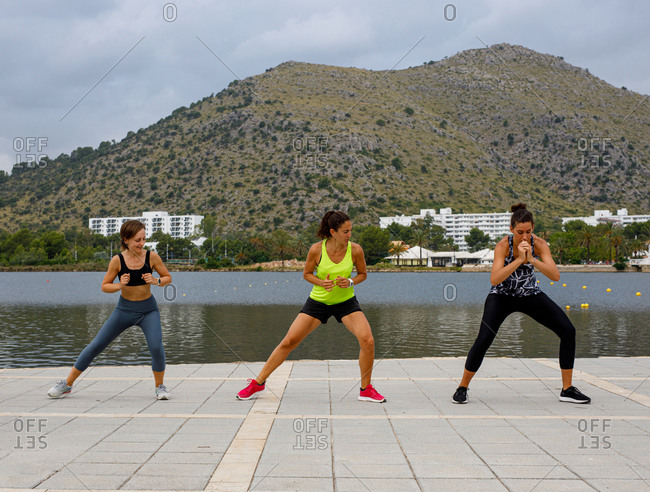 Sportswomen moving actively while doing cardio workout together on embankment on sunny day