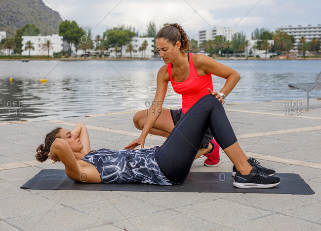 Focused female athlete lying on mat and doing abdominal crunches under supervision of coach during workout on promenade near lake
