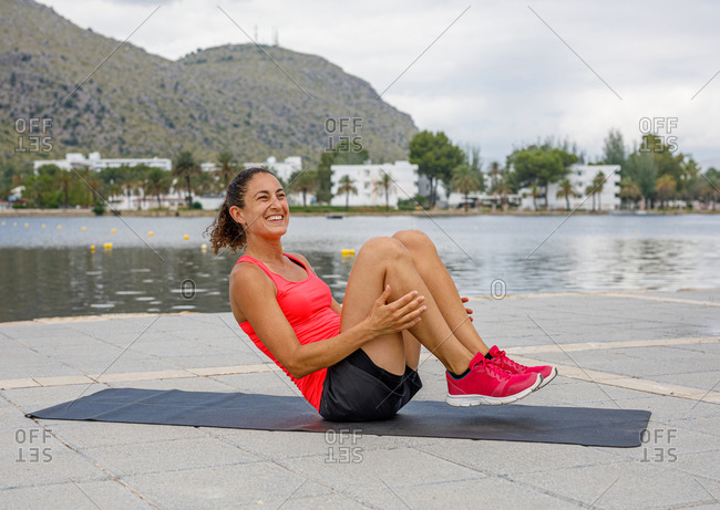 Cheerful female athlete in sportswear lying on mat on embankment and doing abdominal crunches during active training in summer while looking away