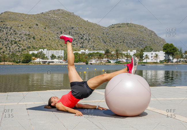 Side view of determined female athlete lying on mat and leaning on fit ball while raising leg and doing exercises during training on embankment in summer