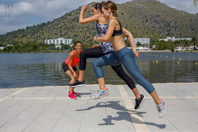 Side view of sporty women in activewear running together along promenade during cardio training and competing with each other under supervision of coach