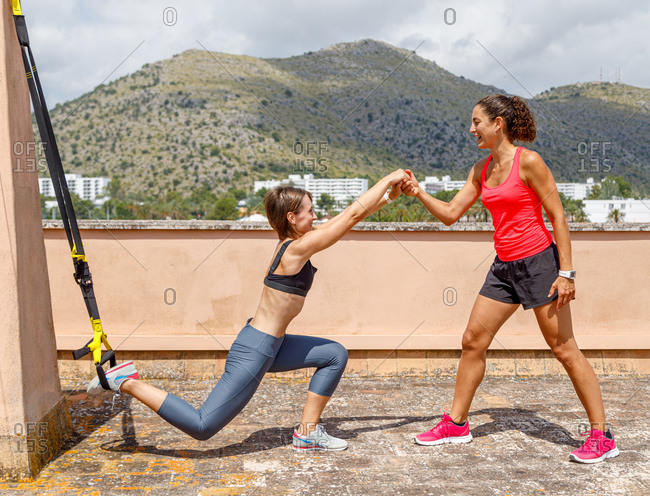 Side view of smiling female coach holding hand of sportswoman doing lunges with TRX straps during intense training on terrace in summer