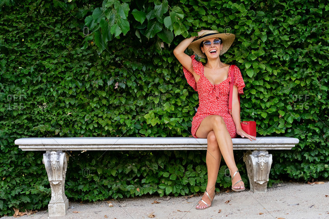 Delighted female in dress and straw hat sitting on stone bench in garden and laughing while looking at camera and enjoying weekend in summer