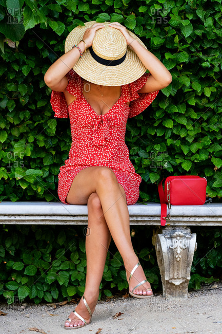 Delighted unrecognizable female in dress and straw hat sitting on stone bench in garden enjoying weekend in summer