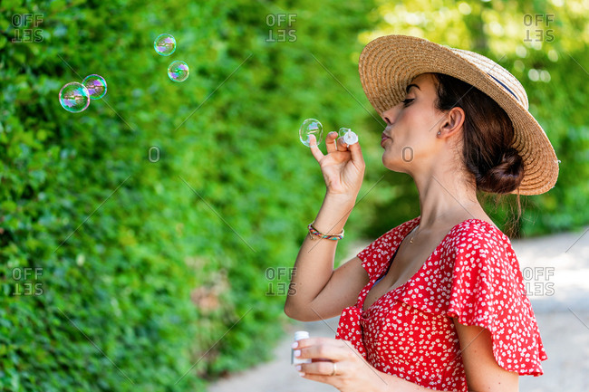 Side view of tranquil female in summer outfit standing in lush garden and blowing soap bubbles while having fun at weekend